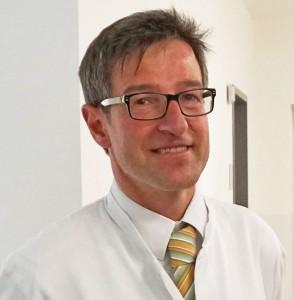 Foto von Dr. Bernd Köster in weißem Kittel auf der Station IDA des RKK Klinikums