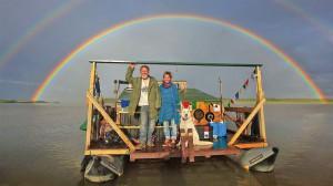 Foto von Mario und Ramona Goldstein mit ihrem Hund auf dem selbstgebauten Floß. Im Hintergrund ein doppelter Regenbogen