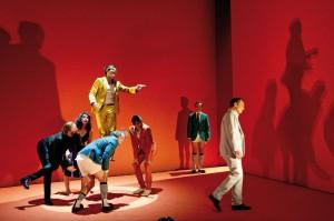 """Szenenbild mit sieben Schauspielern aus """"Caligula"""" im Theater Basel. Manche tragen keine Hosen, ihre Körper werfen große Schatten auf die rote Wand im Hintergrund"""