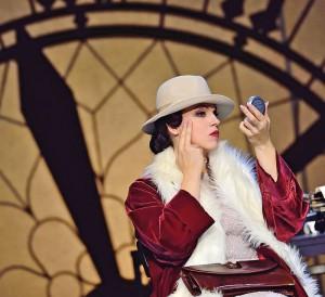 Foto von Opernsängerin Katerina Hebelková als Primadonna, sie sitzt vor einem großen Ziffernblatt und schminkt sich