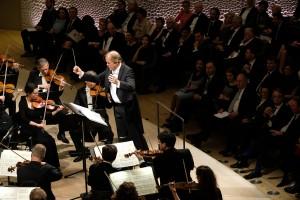 Foto des Eröffnungskonzerts in der Elbphilharmonie. Im Bildzentrum Dirigent Thomas Hengelbrock.