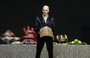 """Szenenbild aus """"Don Giovanni"""" im Theater Basl, es zeigt den Schauspieler Riccardo Fassi mit einem Telefonbuch vor einem Buffet"""