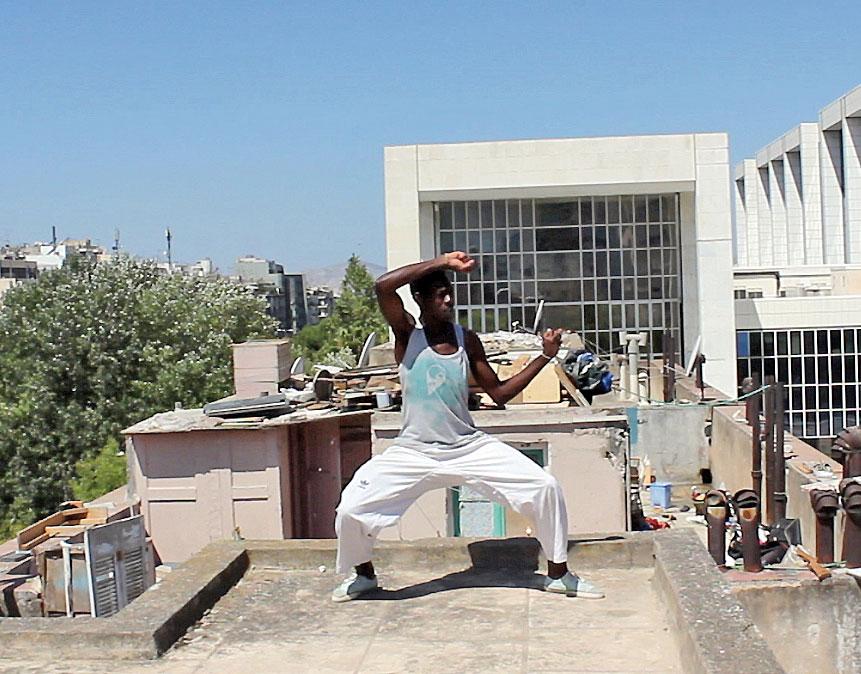 Foto eines dunkelhäutigen Mannes auf einem Hausdach. Er vollführt eine Bewegung die an Tai-Chi oder Yoga erinnert.