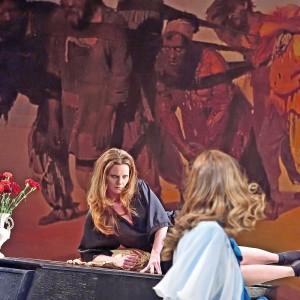 Szenenfoto aus Wassa Schelesnowa: Die Schauspielerinnen Melanie Lüninghöner und Marie Bonnet vor einem Wandgemälde ausgebeuteter Arbeiter